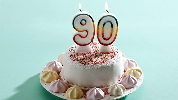 Geburtstagstorte mit Marshmallows und bunten Perlen verziert. Darauf brennen zwei Kerzen mit der Ziffer 90.