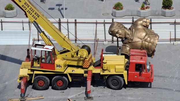 Ein Kran steht neben einer riesigen Bronze-Statue