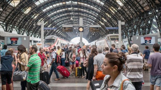 Blick in den Bahnhof Milano, in dem zahlreiche Reisende zu sehen sind.