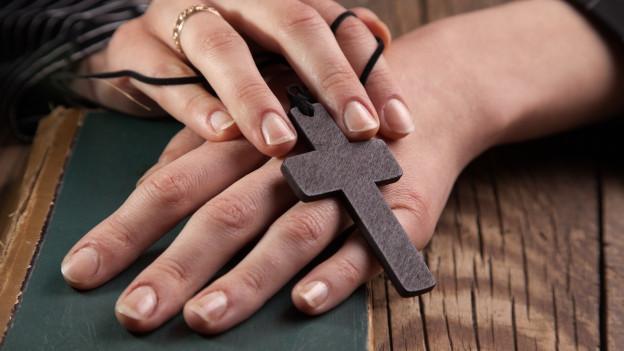 Hände mit einem christlichen Kreuz.
