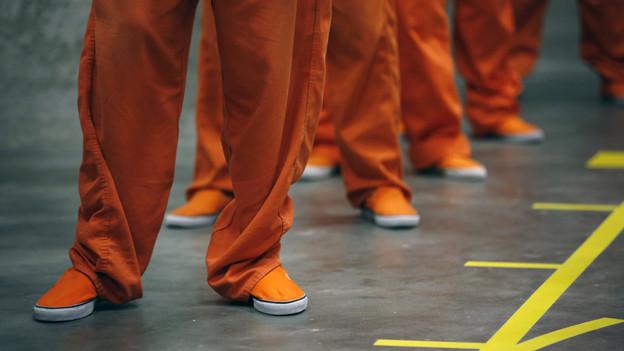 Die Beine eines Sträflings in orangen Hosen.