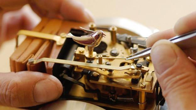 Ein metallisches Gerät mit einem Vogel aus Metall wird mit einer Pinzette bearbeitet.