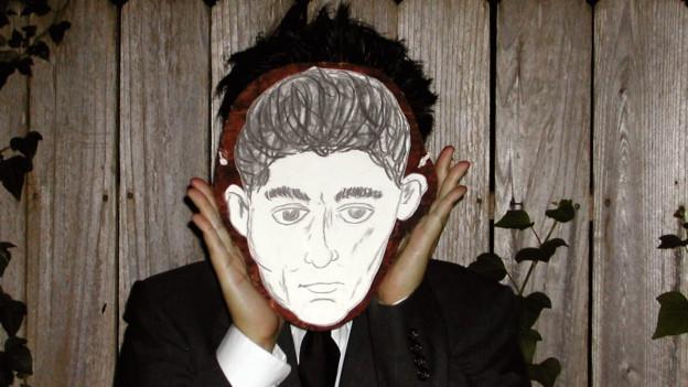 Mann hält schwarzweisse Kafka-Maske vor sein Gesicht.