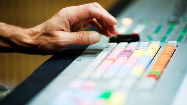 Symbolbild: Hand auf Mischpult im Radiostudio.