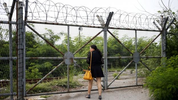 Eine chinesische Touristin steht in Paju, Südkorea, am mit Stacheldraht bestückten Grenzzaun zu Nordkorea.