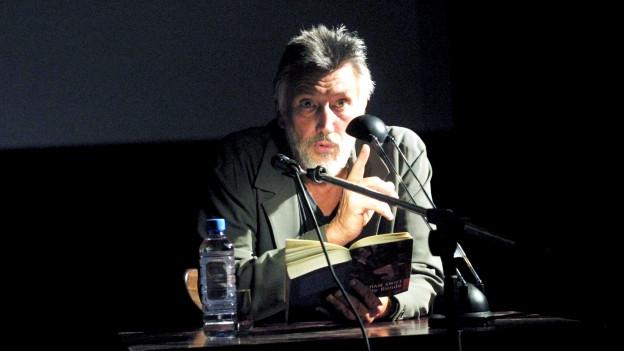 Ein Mann mit grauen Haaren und Bart sitzt an einem Tisch, auf dem ein Mikrophon befestigt ist, und liest aus einem Buch.