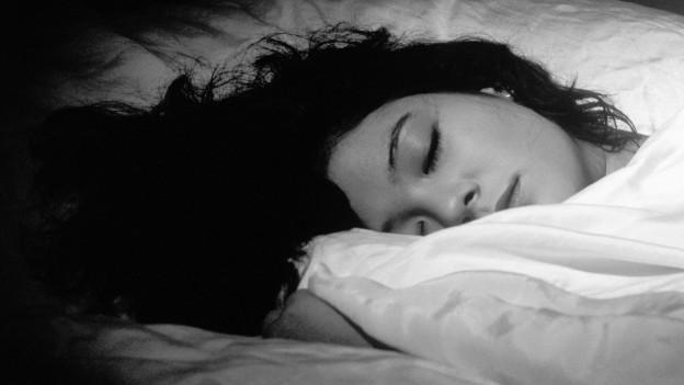 Eine Frau mit schwarzen Haaren liegt im Bett und schläft.
