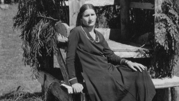 Eine Frau sitzt auf einer Holzkonstruktion.