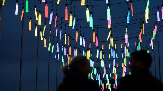Eine Reihe Lampions hängt unter den dunklen Nachthimmel.