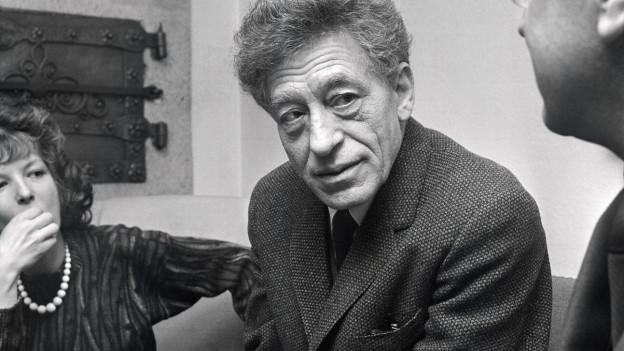 Schwarzweissfoto: Der Maler Albert Giacometti zwischen einem Mann und einer Frau.