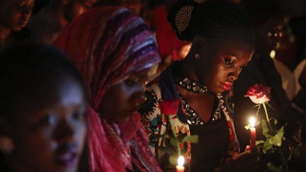 Trauerfeier: Eine schwarze Frau, deren Gesicht von einer brennenden Kerze erhellt wird, hält eine Blume in der Hand.