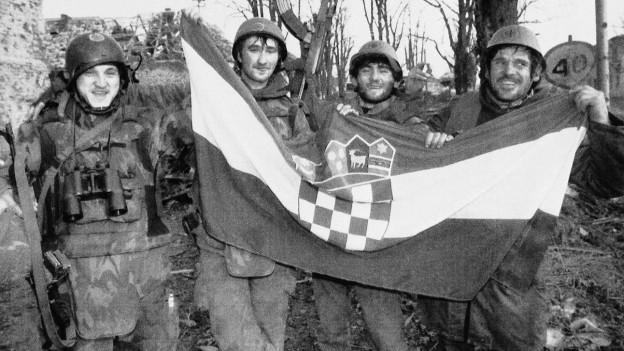 Vier Soldaten halten die kroatische Flagge
