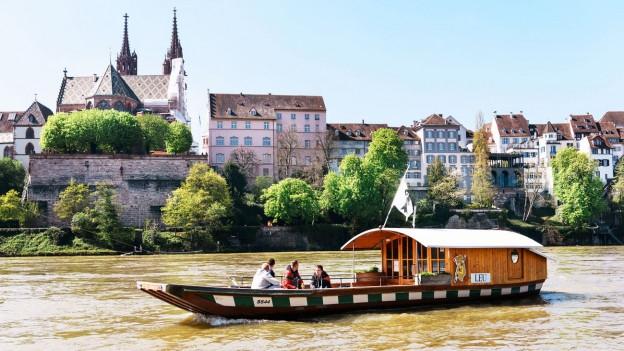 Die Münsterfähre «Leu» im Rhein in Basel. Im Hintergrund sieht man das Münster.
