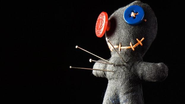 In einer selbst genähten Puppe stecken Nadeln drin.
