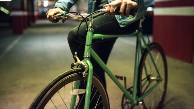 Ein Fahrrad von vorne in der Nahaufnahme auf der Stange sitzt jemand.