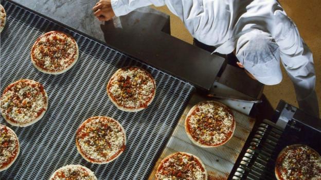 Arbeiter an einem Fliessband mit Pizza