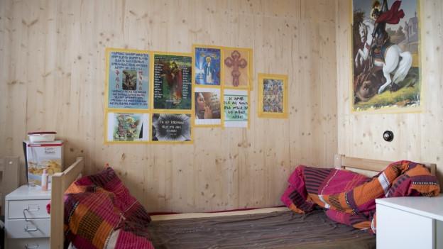 ein ungemachtes Bett, an der Wand hängen bunte Poster
