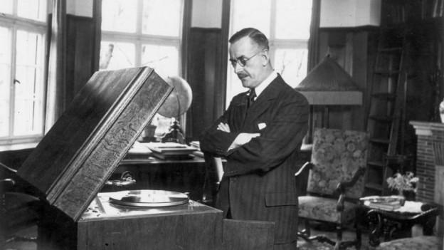 Ein Mann steht in einer Wohnung mit verschränkten Armen vor einem Grammophon