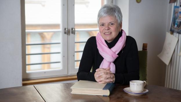 Frau mit kurzen grauen Haaren sitzt an einem Küchentisch und lächelt in die Kamera