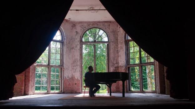 Mann an einem Klavier