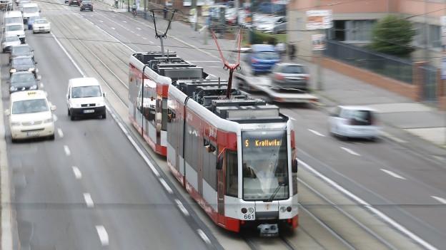 Eine rot-weisse Strassenbahn im Verkehr