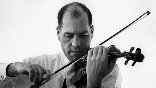 Ein Mann in schwarz-weiss hat eine Geige in der Hand
