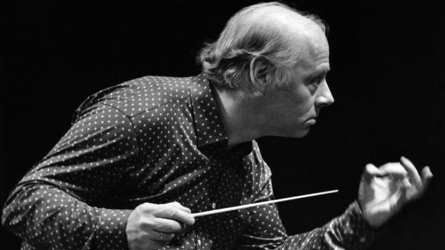S/W-Bild: Mann mit konzentriertem Blick von der Seite fotografiert. Er ist gerade dabei, ein Orchester zu dirigieren, welches im Bild aber nicht zu sehen ist.