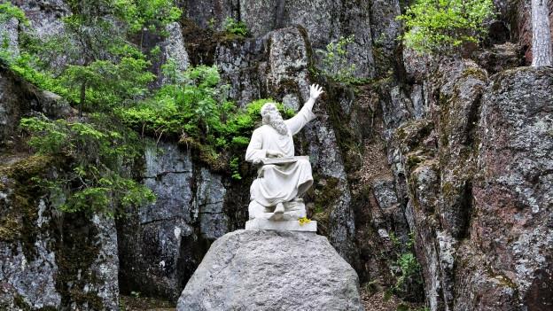 Weisse Skulptur eines bärtigen Mannes auf einem Felsbrocken