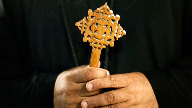 Das koptische Kreuz, in der Hand eines ägyptischen Mönchs.