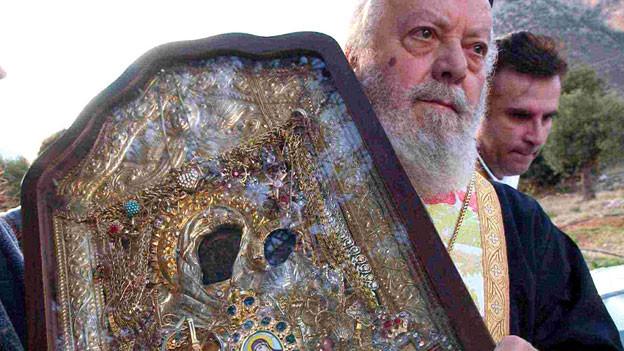 Die Fotografie zeigt einen Mann, der eine reich geschmückte Ikone in Gold trägt.