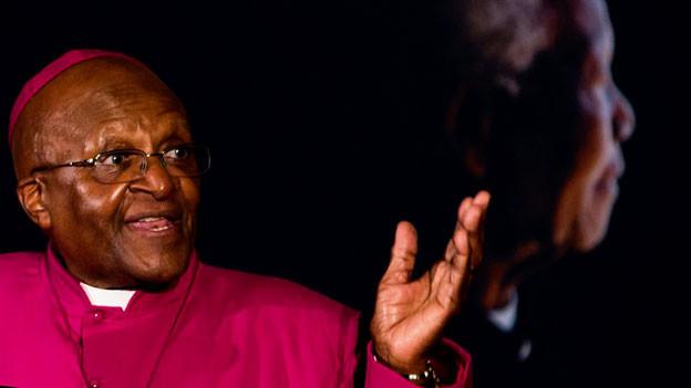 Desmond Tutu im Bild. Im Hintergrund eine Projektion von Nelson Mandela.