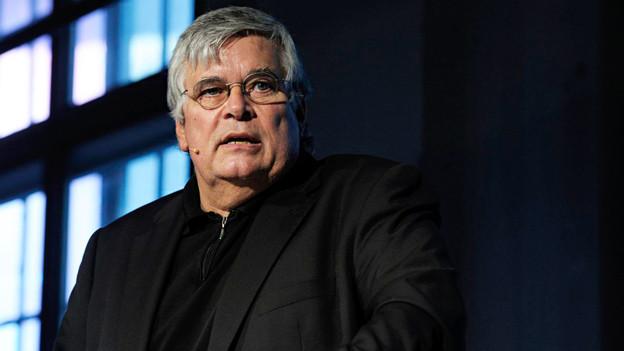 Porträt eines Mannes mit Brille und grauen Haaren.
