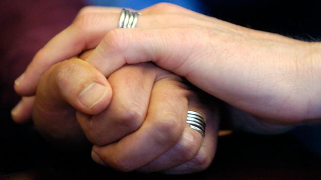 Zwei Männerhände tragen Eheringe und umfassen sich.