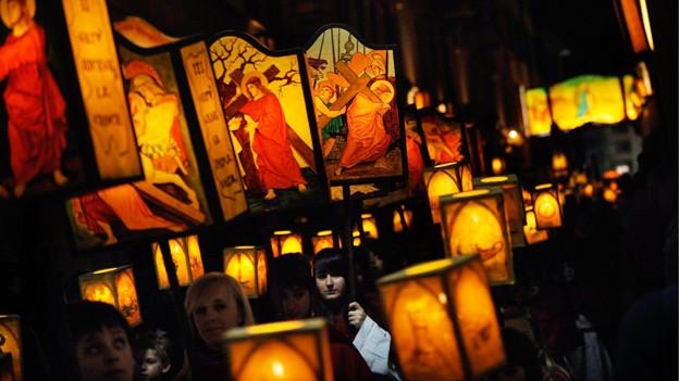 Menschen tragen Laternen mit religiösen Motive durch die Nacht.