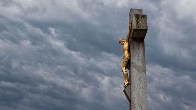 Ein goldener Jesus an steinernem Kreuz vor bewölktem Himmel.
