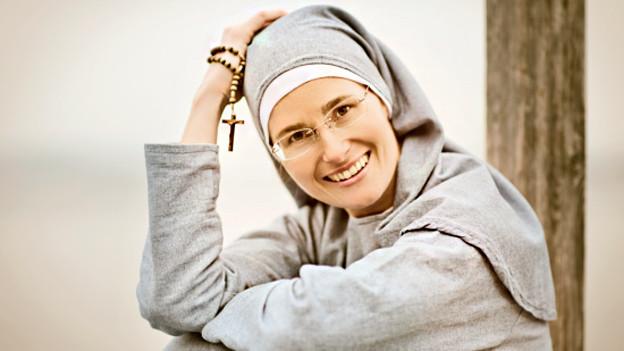 Eine junge Nonne in grauem Gewand.