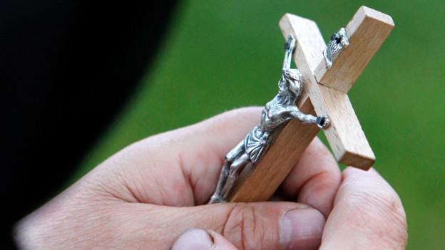 Frau hält Kreuz in der Hand.