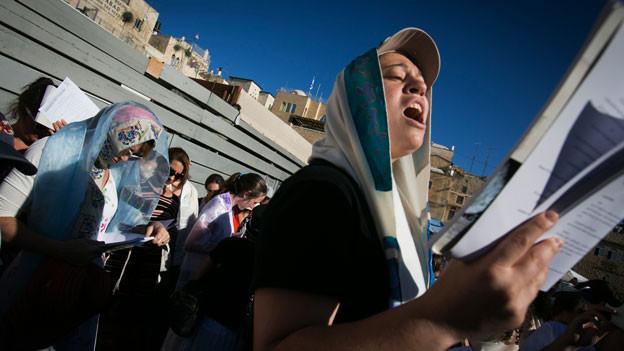 Eine Frau mit Gebetsmantel betet an der Klagemauer.