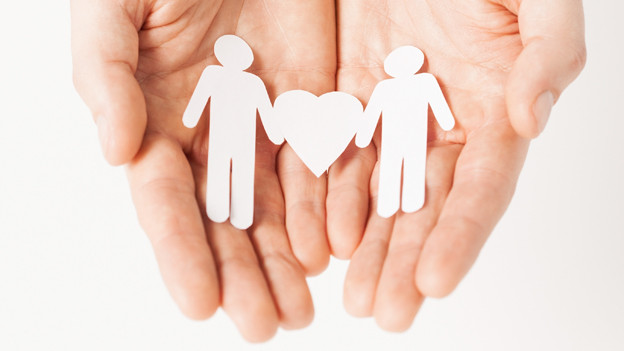 Zwei Hände halten einen Scherenschnitt, der ein männliches Paar zeigt.