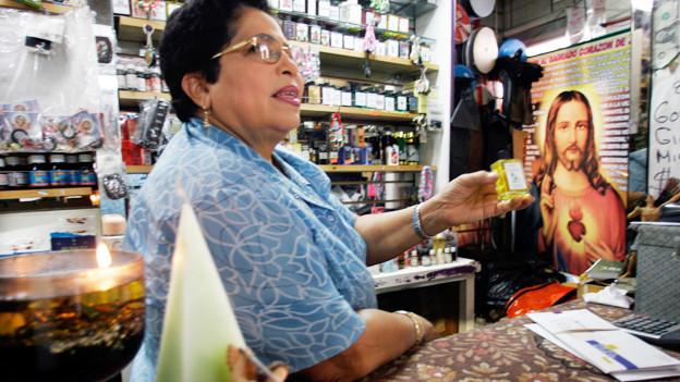 Eine Frau steht in einem voll bepackten Laden vor einem Jesus-Bild.