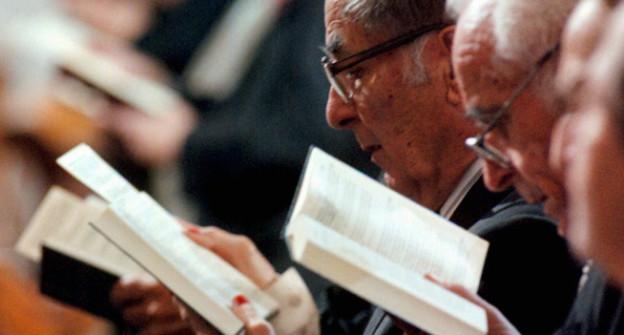 Männer mit LIederbuch singen in der Kirche.