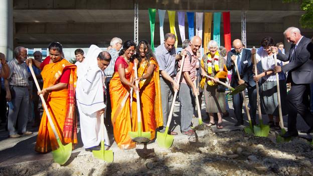 Menschen mit verschiedenen Religionen eröffnen die Bauarbeiten.