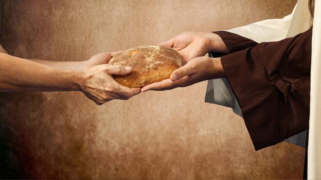 Ein Bettler erhält Brot.