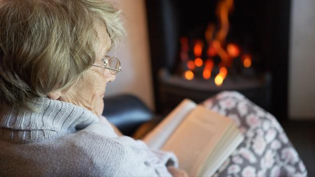 Eine Frau liest ein Buch vor dem Kaminfeuer.