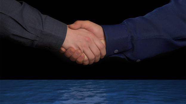 Zwei Menschen, die sich die Hand geben.