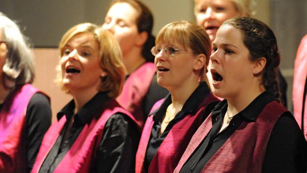 Frauen singen in einer Kirche.