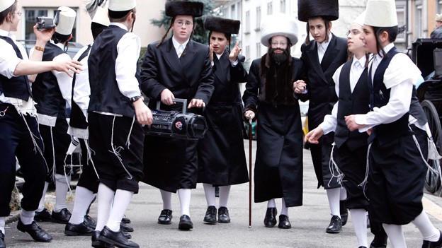 Jüdische Jungen feiern verkleidet auf der Strasse mit Musik und Kamera.