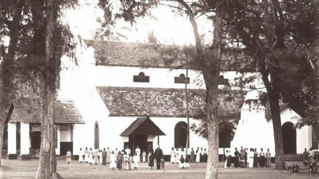 Altes Foto einer grossen Kirche, davor stehen Menschen.