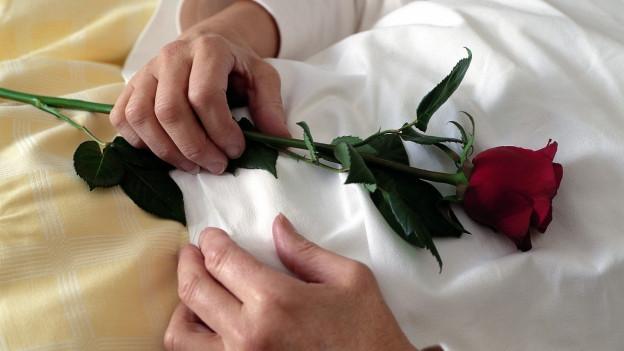 Eine Frau liegt auf dem Totenbett mit einer Rose in der Hand.