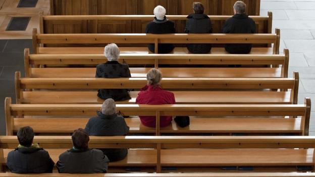Menschen sitzen auf Kirchenbänken.